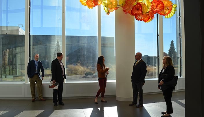 Image with caption: As part of the visit, hospital officials toured the Chihuly Sanctuary in the Fred & Pamela Buffett Cancer Center.