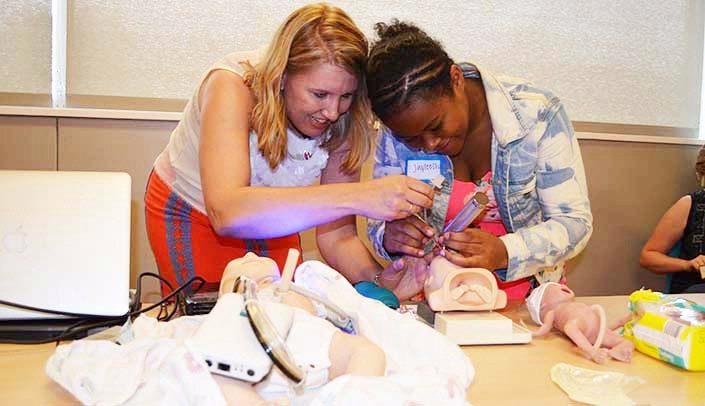 Image with caption: Ann Anderson Berry, M.D., Ph.D., a neonatologist at UNMC, shows Jayleesha Cooper how to resuscitate a tiny infant.