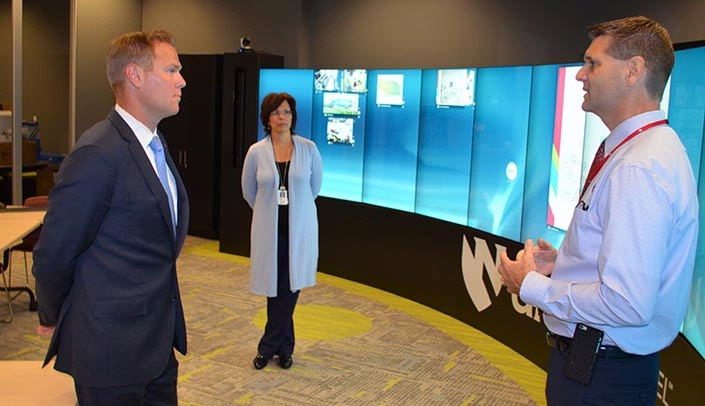 Image with caption: Sen. Brett Lindstrom, left, meets with Suzanne Torroni, center, and Ben Stobbe, right, at the iEXCEL Visualization Hub.