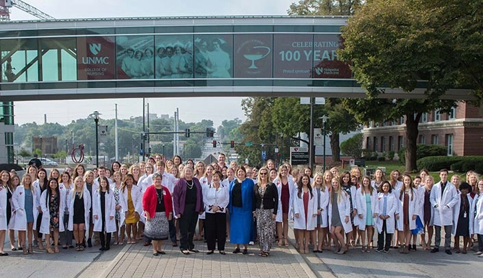 Image with caption: The 2017 entering class of the University of Nebraska Medical Center College of Nursing Omaha Division, stands in front of a banner featuring the entering class of 1917. The banner, which stretches across 42nd St. near Emile St., recognizes the college's 100th anniversary.