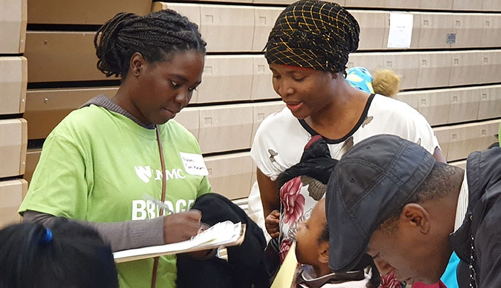Image with caption: Public health student Na-Omi Hassane Dan Karami, in green T-shirt, interprets for a French speaking family at the Fall Refugee Health Fair held Nov. 2, 2019 at Benson High School. Na-Omi worked as a navigator during the health fair as part of the UNMC College of Public Health student-led Bridge to Care program, which is one of the many community service activities that led to the recognition by the Association of Schools and Programs of Public Health.