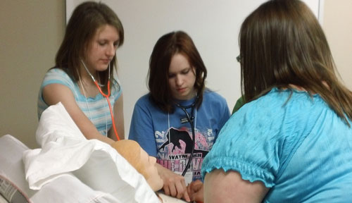 Image with caption: Three students check for vital signs at nursing camp.