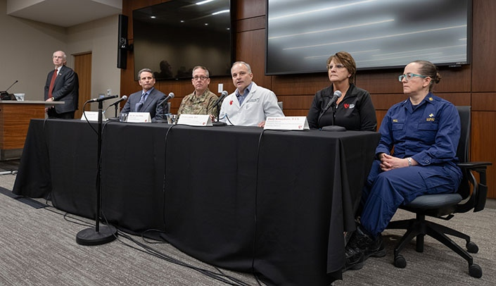 Image with caption: From left, UNMC Chancellor Jeffrey P. Gold, M.D.; Eric Kasowski, M.D., U.S. Centers for Disease Control and Prevention; Maj. Gen. Daryl Bohac, adjutant general, Nebraska National Guard; James Lawler, M.D., director, international programs and innovation, UNMC Global Center for Health Security; Shelly Schwedhelm, executive director, Nebraska Medicine Emergency Management and Biopreparedness; and Capt. Dana Hall, Office of the Assistant Secretary for Preparedness and Response, speak to the media Thursday morning about the Americans arriving in Nebraska to be quarantined at Camp Ashland.