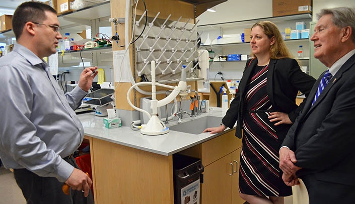 Image with caption: Legislative candidate Wendy DeBoer talked about the work being done in the Fred & Pamela Buffett Cancer Center with Nicholas Woods, Ph.D., left, and vice chancellor Bob Bartee, right.
