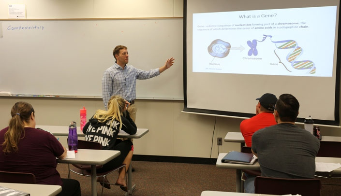 Image with caption: Eric Tom, Ph.D., teaches undergraduate students at Metropolitan Community College.