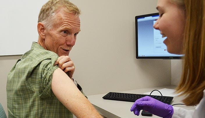 Image with caption: On Sept. 20, College of Pharmacy Dean Courtney Fletcher, Pharm.D., made sure he got his flu shot at the student-run clinic.