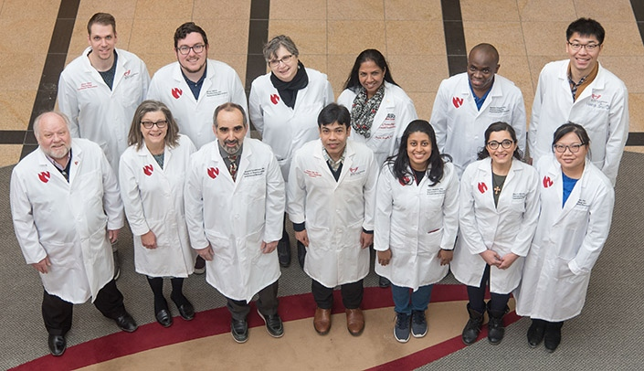 Image with caption: Members of the UNMC research team included: Back row (left-right) - James Hilaire, Brady Sillman, Ph.D., Larisa Poluektova, M.D., Ph.D., Santhi Gorantla, Ph.D., Benson Edagwa, Ph.D., and Hang Su; Front row -- R. Lee Mosley, Ph.D., JoEllyn McMillan, Ph.D., Howard Gendelman, M.D., Prasanta Dash, Ph.D., Saumi Mathews, Ph.D., Mary Banoub, and Zhiyi Lin.  Missing from photo - Aditya Bade, Ph.D. and Nagsen Gautam, Ph.D.