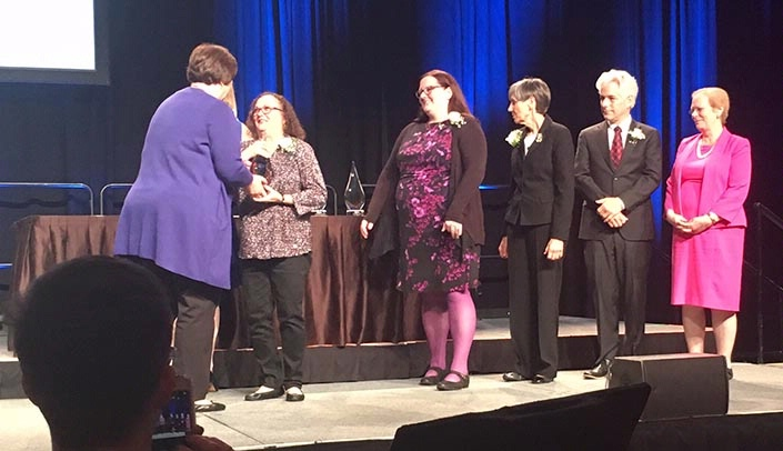 Image with caption: Mary Helms, second from left, receiving her award from Medical Library Association President Theresa Knott, left.