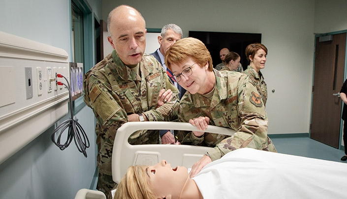 Image with caption: From left, Maj. Gen. Robert Miller, M.D., the Air Force director of medical operations and research, and Lt. Gen. Dorothy Hogg, U.S. Air Force Surgeon General, check out a simulation suite during their tour of UNMC.