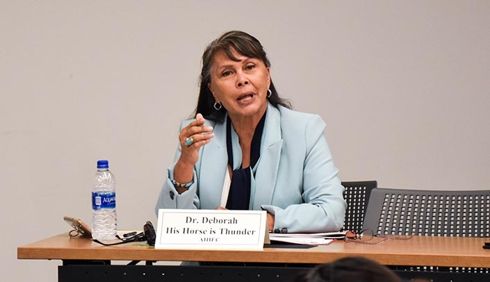 Image with caption: Deboarah His Horse Is Thunder, Ph.D., of the American Indian Higher Education Consortium, speaks at the event. (Photo by Grace Cai, UNMC Center for Reducing Health Disparities)