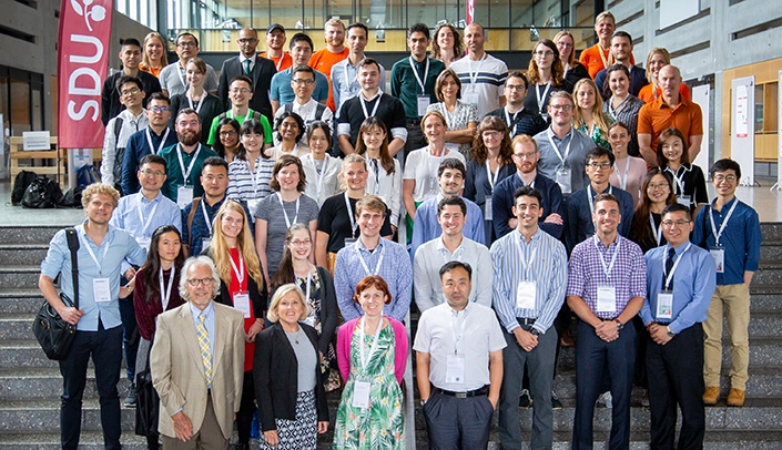 Image with caption: Attendees at this year's International Student Research Forum pose at the University of Southern Denmark in Odense, Denmark. UNMC coordinators of the ISRF Keith Swarts and  Jayme Nekuda, Ph.D., are at left in the front row.