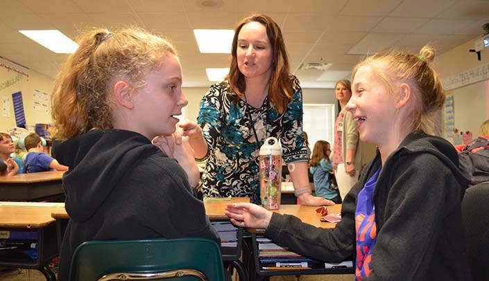 Image with caption: Jacy Vermaas, center, works with children on an exercise design to confuse the brain as the kids attempt to move a finger.