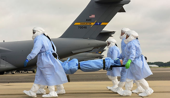 Image with caption: Airmen from the 628th and 375th Aeromedical Evacuation Squadrons transport a simulated highly infectious patient during a training exercise with UNMC-led investigators. (Photo by Airman 1st Class Joshua Maund)