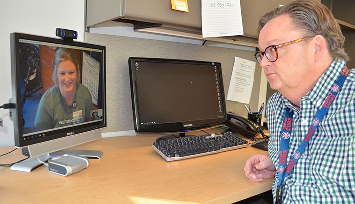 Tom Magnuson, M.D., at right, speaks with a colleague through telecommunication.