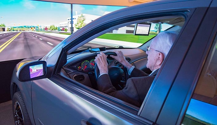 Image with caption: One of the research studies seeking volunteers involves using the advanced driving simulator in the UNMC Mind & Brain Health Labs.
