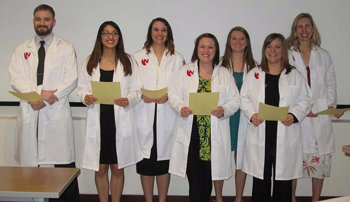 Image with caption: Accelerated nursing students at the UNMC Kearney Division participated in the Nightingale White Coat Ceremony March 31. Pictured are (from left): Daniel Nielsen, Ogallala; Estrella Monrroy, Cozad; Melissa Langenberg, Gering; Stephanie Korus, Beatrice; Brandie Janssen, Alma; Kristin Henggeler, Eustis; and Helen Albrecht, Kearney. Not pictured: Keely Envick, Shelton.