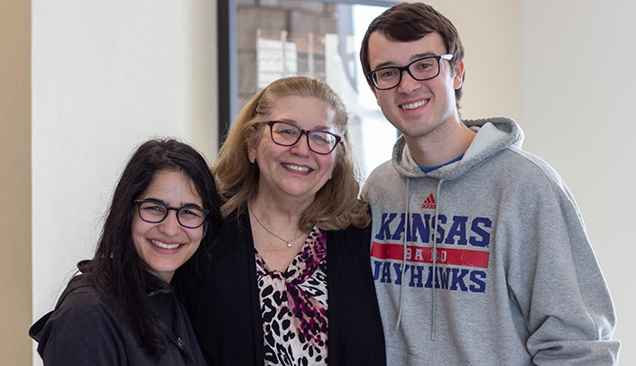 Image with caption: Ricki Otten, center, with students Hannah Tandon, left, and Alex Kolomaya at her retirement tea in December 2019.