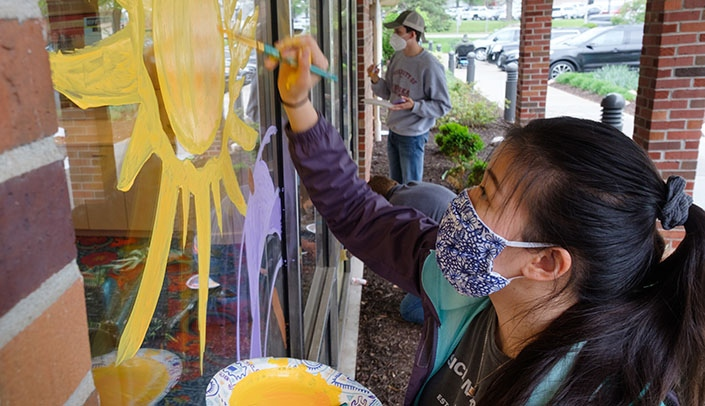 Image with caption: PA student Josephine Ngo paints a window at St. Joseph's Villa nursing and rehab center in Omaha.