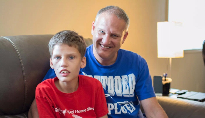 Image with caption: Broc Bartenhagen (left), a 14-year-old from Gretna, Neb., with drug resistant epilepsy, is a potential candidate for the cannabidiol study being conducted at UNMC. He's seen here with his father, Mike Bartenhagen.