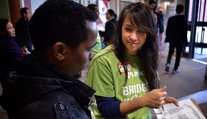 Image with caption: A Bridge to Care volunteer assists a refugee at a previous health fair.