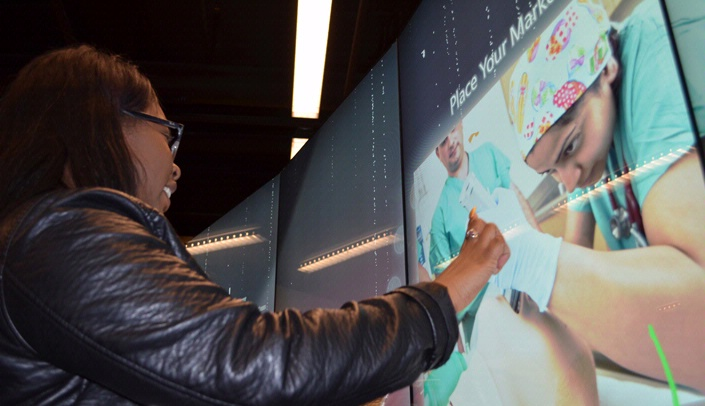 Image with caption: Regis Randolph, a UNL student, explores the multitaction wall.