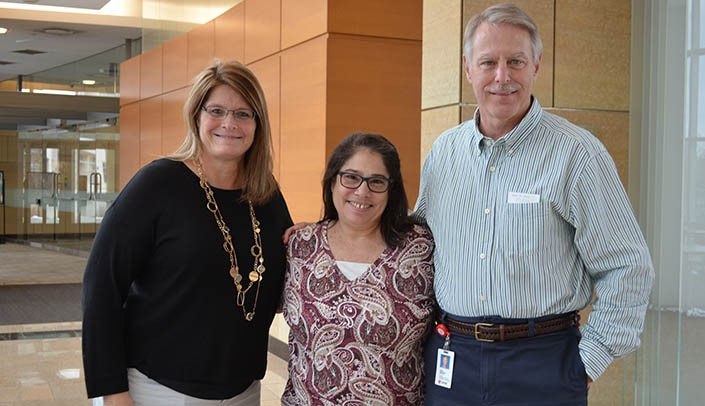 Image with caption: Betty Revers, center, will soon be retiring after a 40-year career at UNMC. She's flanked by two of her colleagues in comparative medicine -- Tricia Rump, business manager, and John Bradfield, D.V.M., director.