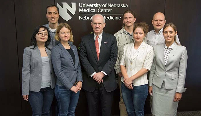 Image with caption: From left, Nadezhda Oyun, Ph.D., Marat Makenov, Ph.D., Tatiana Galinska, Ph.D., UNMC Chancellor Jeffrey P. Gold, M.D., Artem Tikunov, Ph.D., Galina Chicherina, Ph.D., Alexander Khilkov and Oxana Belova, Ph.D.
