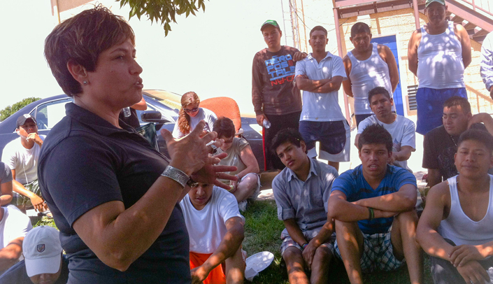 Image with caption: Aida Olivas, with the Nebraska Migrant Education Program, introduces the study team to a group of migrant workers.