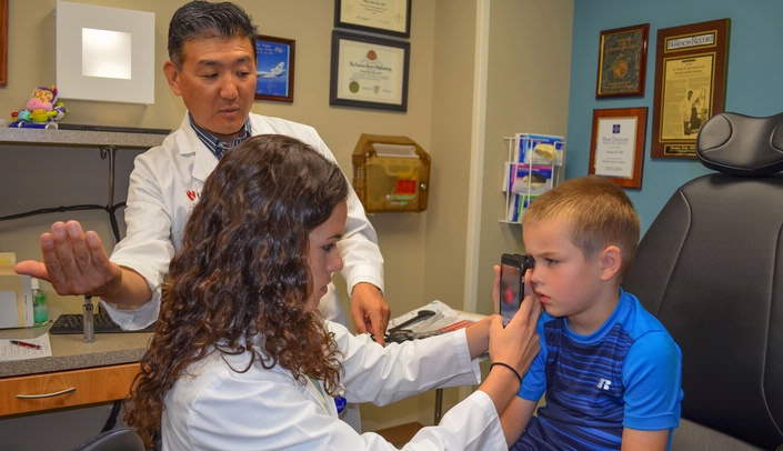 Liana Morales, a student in the UNMC Summer Undergraduate Research Program, does an eye exam using the smartphone camera attachment on Barrett Kumke, while pediatric ophthalmologist Donny Suh, M.D., oversees the procedure.