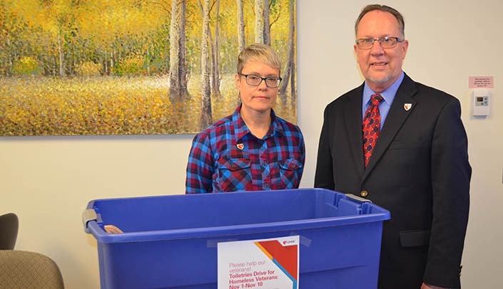 Image with caption: Fran Higgins, Wayne Mathews and an empty donation bin. UNMC students, faculty and staff can help the College of Allied Health Professions' Physician Assistant Program fill it.