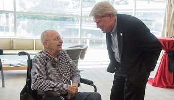 Image with caption: At left, former UNMC Chancellor Charles Andrews, M.D., talks to Bob Bartee, vice chancellor for external relations, at a retirement party for Bruce Buehler, M.D., in 2018.