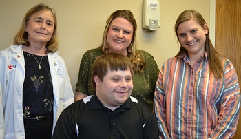 Image with caption: Niko, in front, visits with (from left) Cindy Ellis, M.D., Maggie Neujahr and Lisa Neitzke, Ph.D.