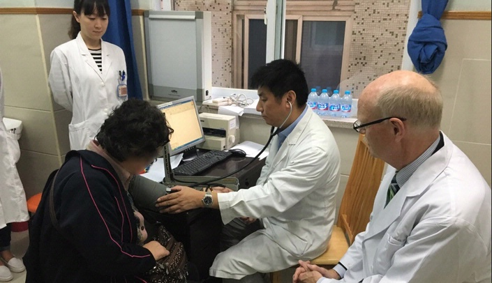 Image with caption: Michael Sitorius, M.D., chairperson for the Department of Family Medicine, participates in a patient consultation at Yangpu Hospital in Shanghai with graduates from UNMC's Family Medicine Leadership Course. (Consent for photo obtained by Yangpu Hospital staff.)