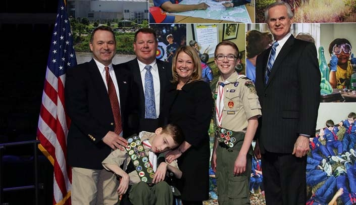 Image with caption: From left, back row: Boy Scouts of America-Mid-America Council Chairman Drew Blossom, Carl Falk, Kim Falk, Andrew Falk and Lt. Gov. Mike Foley; front row, Ethan Falk.