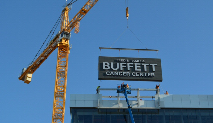 Image with caption: Workers put the sign on the south side of the Fred & Pamela Buffett Cancer Center into place.