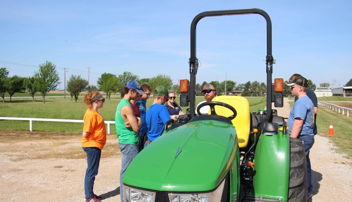 Image with caption: UNMC graduate student Dan Kent (center) discusses with young farmers the importance of seat belts and rollover protection structures.
